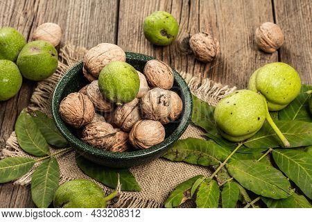 Ripe Brown And Unripe Green Walnuts In A Bowl. Old Wooden Background, Close Up