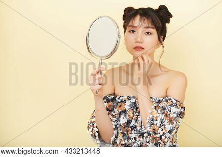 Sad Young Woman Standing With Magnifying Glass Looking For Pimples On Her Chin