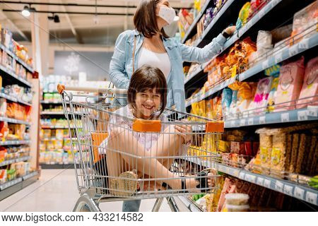Joyful Girl Happy Sitting Inside The Grocery Cart With Crossed Legs While Her Mother In A Medical Ma