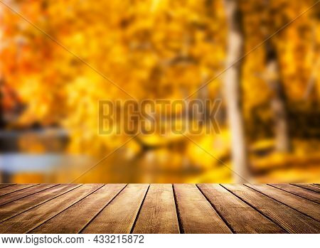 Wooden Table Top On Blur Autumn Background. Autumn Golden Abstract Background With Bokeh Light.