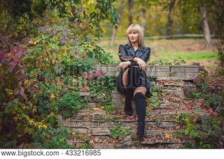Young Woman With Bob Haircut And Fringe In A Black Leather Jacket And High Black Jackboots Is Sittin