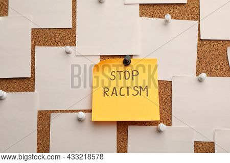 Yellow Paper Note With Phrase Stop Racism Among White Ones Attached To Cork Board