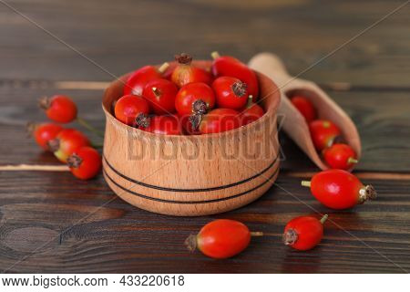 Ripe Rose Hip Berries With Bowl And Scoop On Wooden Table, Closeup