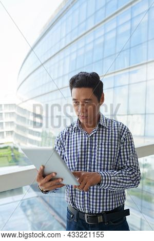 Serious Mature Vietnamese Entrepreneur Reading News Article On Tablet Computer When Standing In Hall