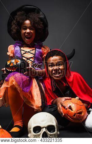 African American Siblings In Halloween Costumes Holding Creepy Pumpkins On Black