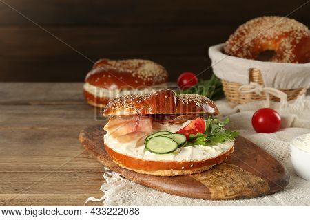 Delicious Bagel With Cream Cheese, Jamon, Cucumber, Tomato And Parsley On Wooden Table