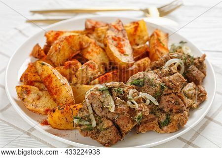 Close-up Of Grilled Pork Shoulder Steaks With Roasted Potato Wedges Seasoning With Paprika And Dill