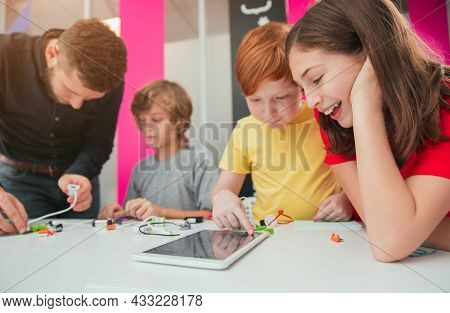 Excited Preteen Boy And Girl Using Tablet Together During Robotics Lesson With Classmates And Teache