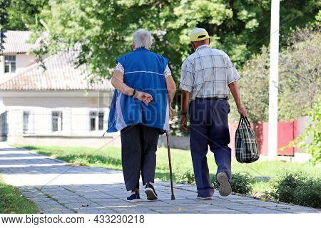 Elderly Couple Walking On A Town Street. Old Man And Woman With Cane, Life In Retirement