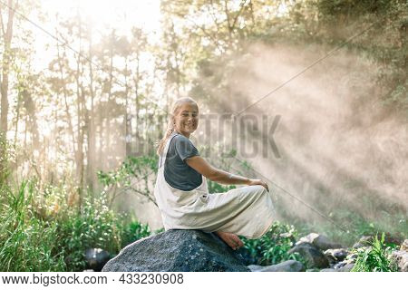 Rays Of Te Sun Illuminating A Smiling Woman Sitting With Her Legs Bent On A Rock In The Rainforest