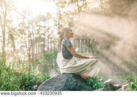 Profile Of A Relaxed Woman Sitting In A Rock In The Rainforest While The Sun Rays Illuminating Her