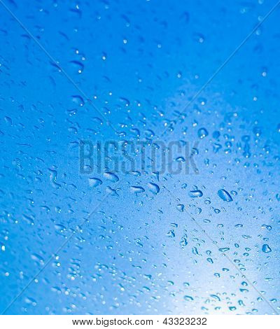 Water drops on blue surface and Reflected of sunlight