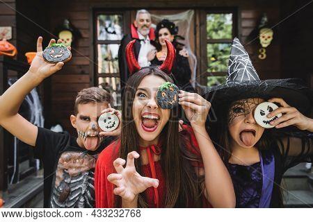Spooky Kids Grimacing Holding Halloween Cookies And Grimacing Near Blurred Parents