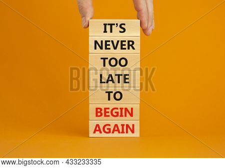 Begin Again Symbol. Wooden Blocks With Words 'it Is Never Too Late To Begin Again'. Businessman Hand