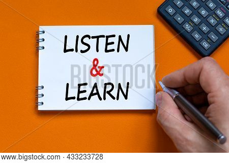 Listen And Learn Symbol. Businessman Writing Words 'listen And Learn' On White Note. Black Calculato