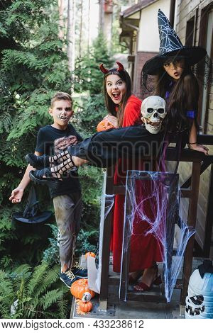 Excited Kids In Spooky Halloween Costumes Grimacing On Cottage Porch