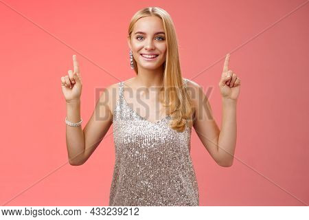 Charming Feminine Tender Blond Woman In Silver Party Dress Raise Hands Pointing Up Smiling Delighted