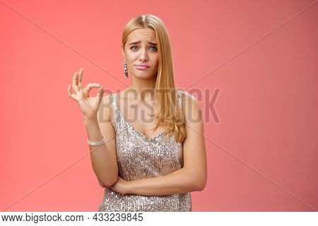 Well Not Bad. Hesitant Unsure Cute Stylish Wealthy Blond Girlfriend In Silver Dress Frowning Cringin