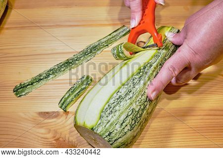 Female Hand Cleans Zucchini  To Peel  On Cutting Board. Cutting Zucchini On Wooden Board Closeup
