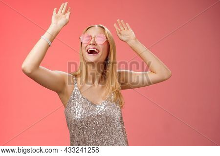 Excited Chilling Energized Young Blond Woman In Silver Stylish Glittering Dress Sunglasses Raise Han