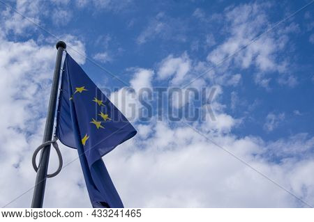 European Union Flag On Blue Sky With White Clouds Background With Copy Space. Eu Flag Flying In Fron