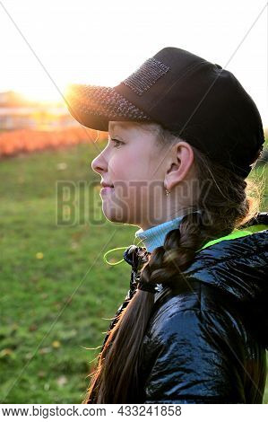 Beautiful Girl With Long Hair, Braided In Braid, And In Black Cap Against  Background Of An Autumn S