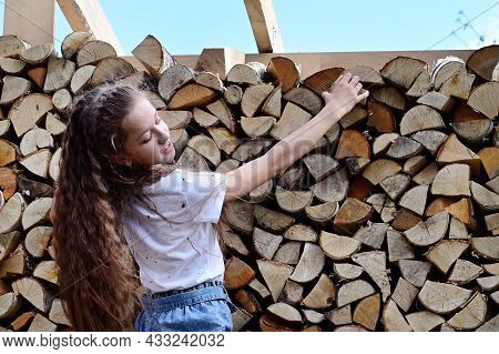 Girl With Long Hair In White T-shirt And Denim Shorts Near Pile Of Firewood. Concept Of Harvesting F