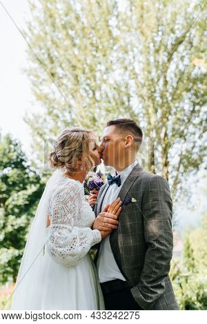 Young Wedding Couple Kissing Outdoors. Groom In Suit Holds Hand Of His Beautiful Bride In White Dres