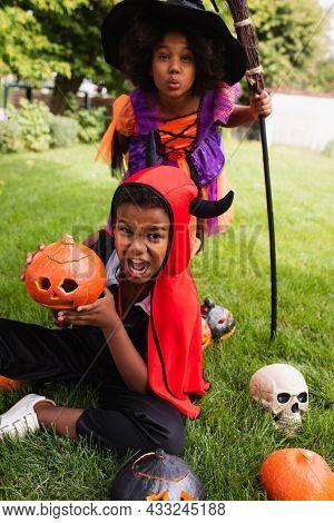 Scary African American Siblings In Halloween Costumes Screaming Near Carved Pumpkins On Backyard