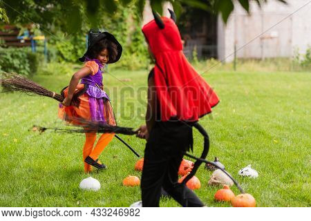 African American Siblings In Halloween Costumes Holding Brooms And Playing On Lawn