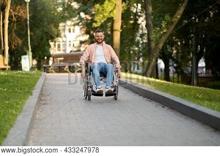 Disabled man in wheelchair rides on a path in park