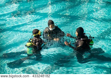 Instructor and divers in aqualungs, dive course
