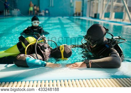 Instructor and divers in aqualungs, diving school