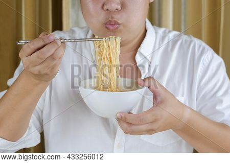 Close Up Of Asian Plus Size Man In White Shirt Using Silver Chopstick To Eating Instant Noodles At H