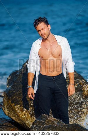 Serious Confident Male With Wet Hair And In White Shirt Standing Near Rock At Seaside And Looking At