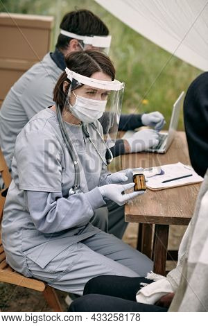 Female nurse in plastic screen mask and gloves sitting at table outdoors and providing medication to migrants