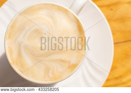 White Coffee In A Cup On A Brown Table