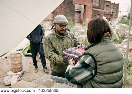 Rear view of social worker in warm vest giving plaid to middle-eastern migrant in glasses and hat outdoors