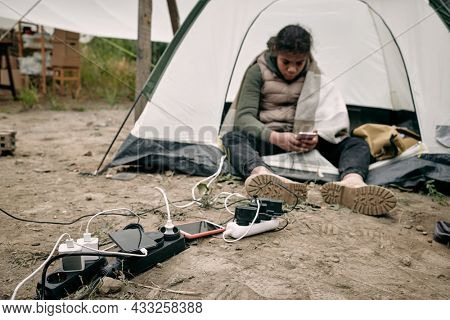 Middle-eastern migrant girl sitting in tent at socket outlets and using smartphone while charging it in refugee camp