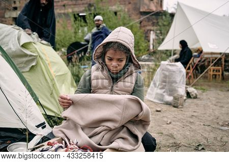 Sad middle-eastern refugee girl in hooded vest holding plaid while freezing in tent camp for migrants