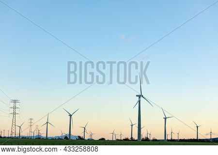 General view of wind turbines in countryside landscape with cloudless sky. environment, sustainability, ecology, renewable energy, global warming and climate change awareness.