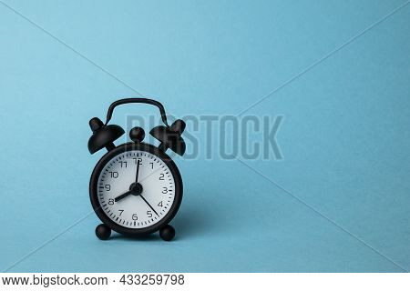 A Small Alarm Clock Ion Blue Background, 8 O'clock