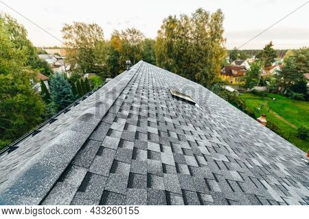 roof of new house with shingles roof-tiles, green foliage background