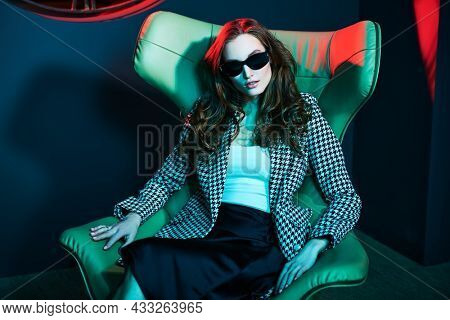 Stunning bossy young woman in fashionable clothing and black sunglasses posing in a leather armchair. Portrait in dark colours of a luxury apartment. Fashion shot.