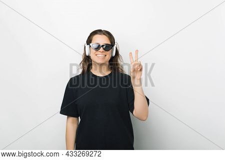 Stylish Female Student Wearing Headphones Is Showing The V Or Peace Gesture.