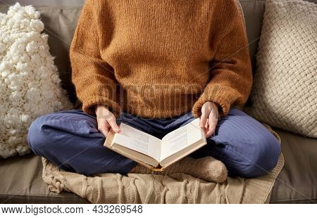 people, season and leisure concept - close up of woman in warm sweater reading book at home