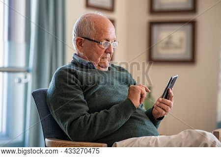 Old man wearing eyeglasses to use smartphone at home. Handsome senior man at home relaxing on couch reading a message on cellphone. Senior sitting alone in his living room and using mobile phone.