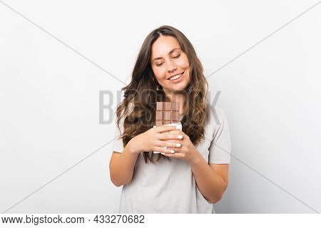 Young Woman Is Tempted To Bite A Piece Of Chocolate She Is Holding.