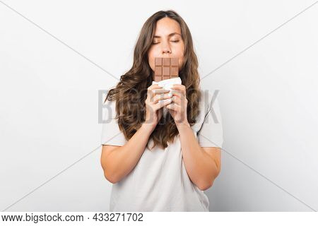 Pretty Woman With Eyes Closed Is Holding A Bar Of Chocolate In Front Of Her Lips.