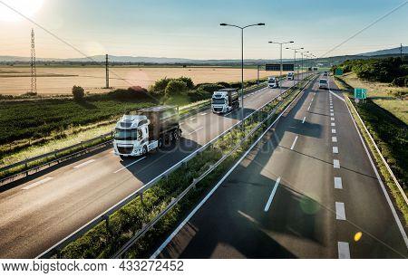 Portable Oxygen Cylinder Canisters Transportationn. Fleet Of Transportation Trucks Driving On Highwa